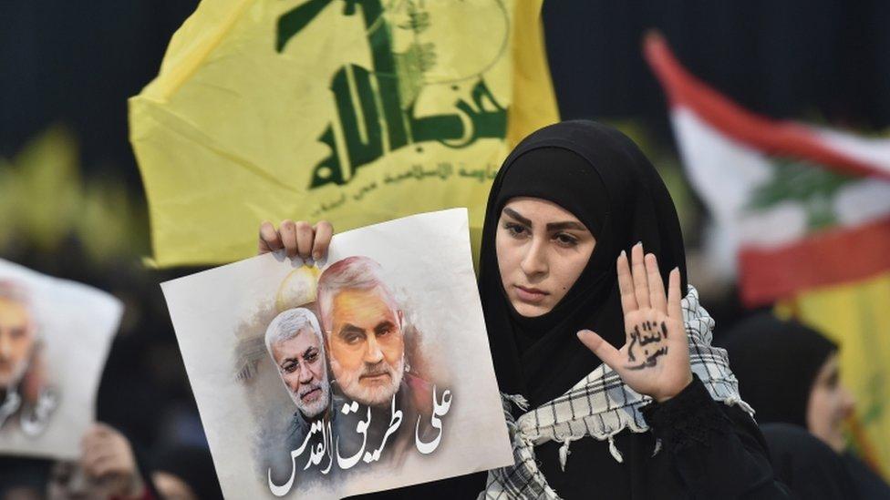 واحدة من أنصار حزب الله ترفع علم الحزب وصورة لقاسم سليماني وأبو مهدي المهندس
