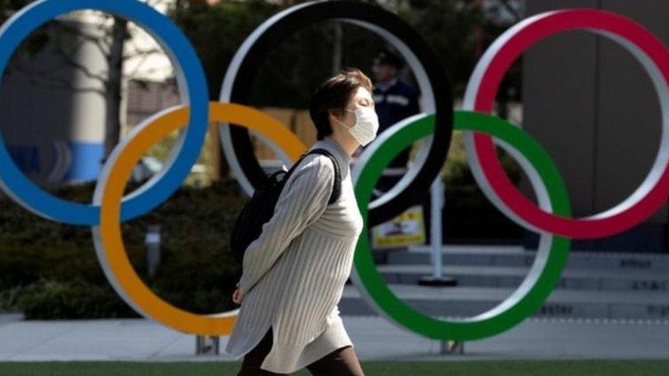 امرأة ترتدي كمامة أمم شعار الألعاب الأولمبية