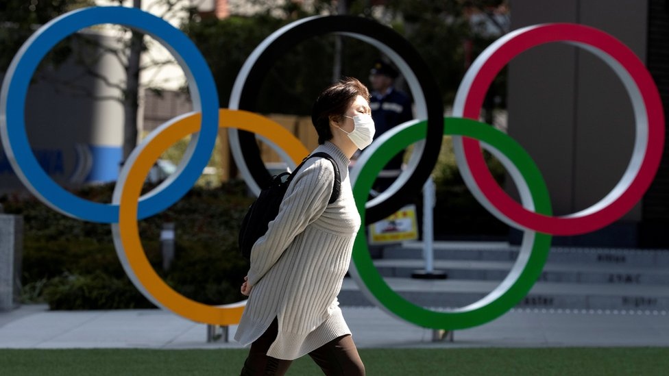 يابانية ترتدي قناعا طبيا أثناء مرورها بجوار شعار الألعاب الأولمبية في طوكيو