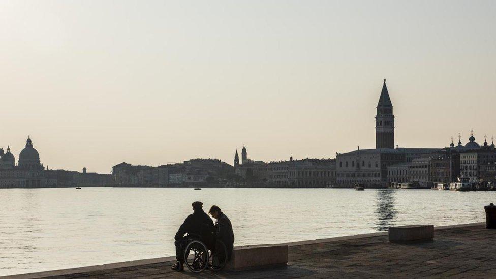 شخصان يجلسان أمام بحيرة