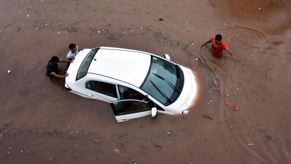 مجموعة من الأشخاص وسيارة وسط مياه كثيرة