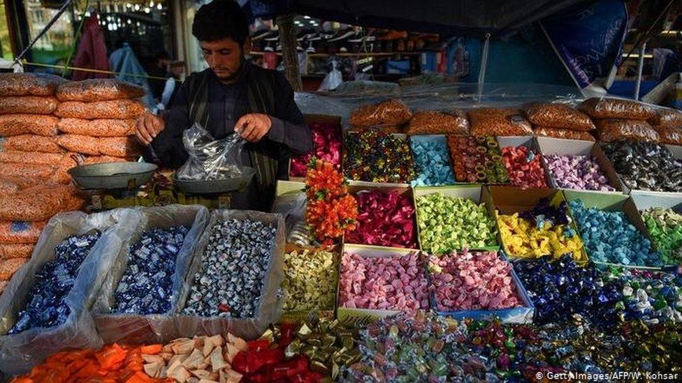معروضات من الحلوى وتاجر ينصب الميزان