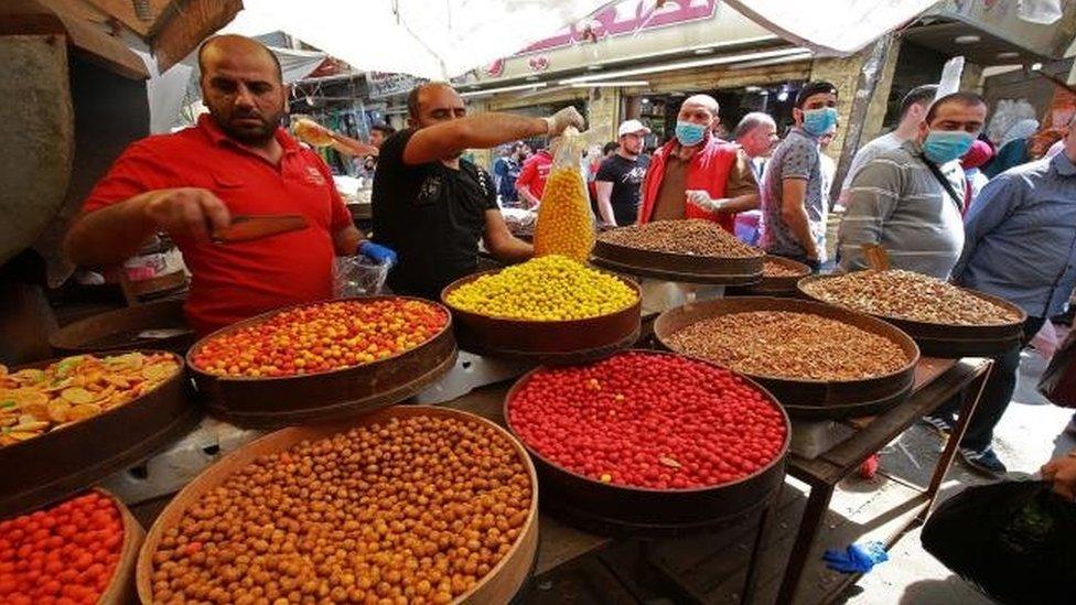 أشخاص يرتدون كمامات في أحد الأسواق