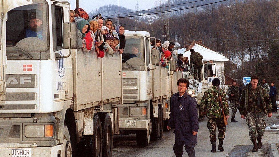 جنود يشرفون على عربات تابعة للأمم المتحدة وعلى متنها نسوة وفتيات وأطفال