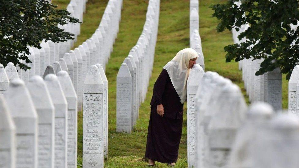 امرأة تقبّل شاهد مقبرة