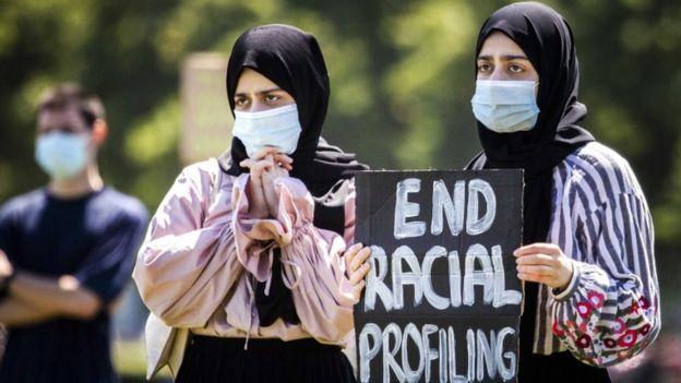 فتاتان تحملان لافتة كتب عليها أنهوا العنصرية