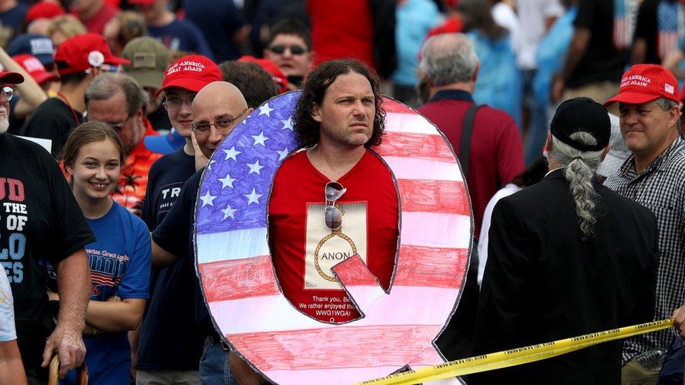 رجل يحمل علامة كيو في تجمع انتخابي مؤيد لترامب