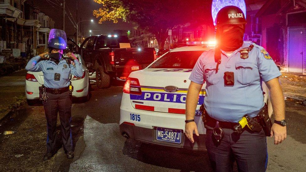 شرطي يحرس شاحنة محملة ببعض المسروقات.