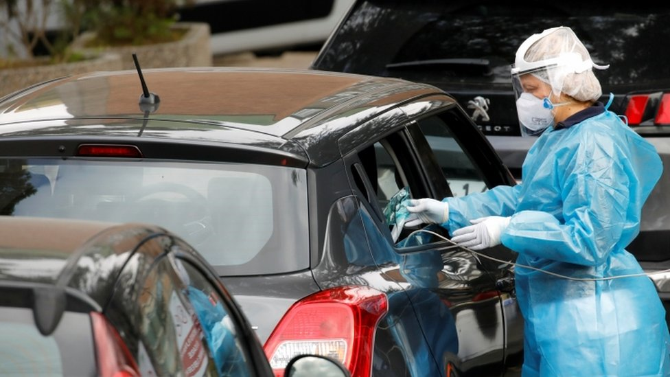 عامل طبي يعطي قناع أكسجين لمريض في سيارة في نابولي، إيطاليا