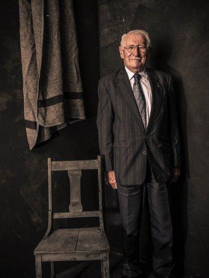 صورة شخصية لإدي جاكو مع كرسي وبطانية مثل تلك التي كان يمتلكها في معسكر أوشفيتز
