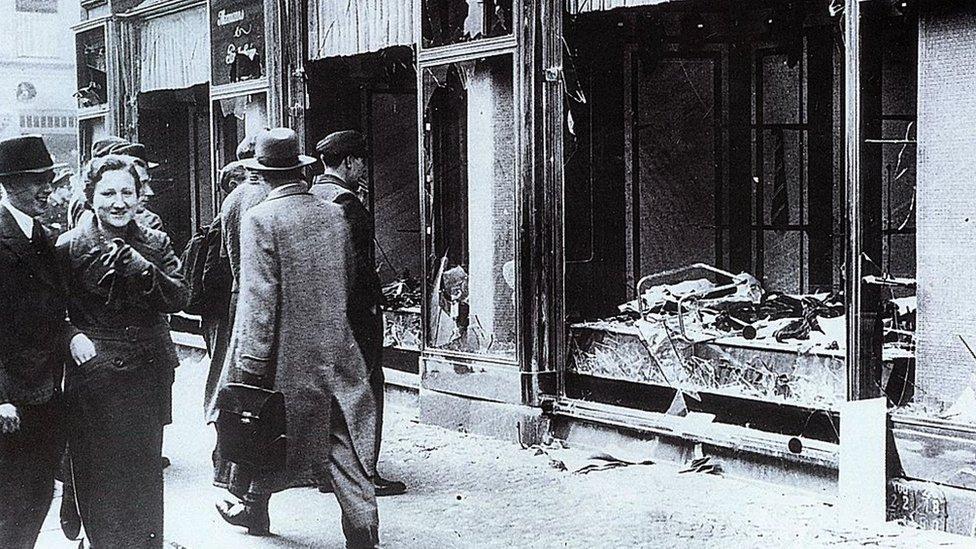مشاة ينظرون إلى زجاج النوافذ والمحال التجارية المملوكة لليهود والتي تم تدميرها خلال ما بات يعرف بليلة الكريستال في ألمانيا