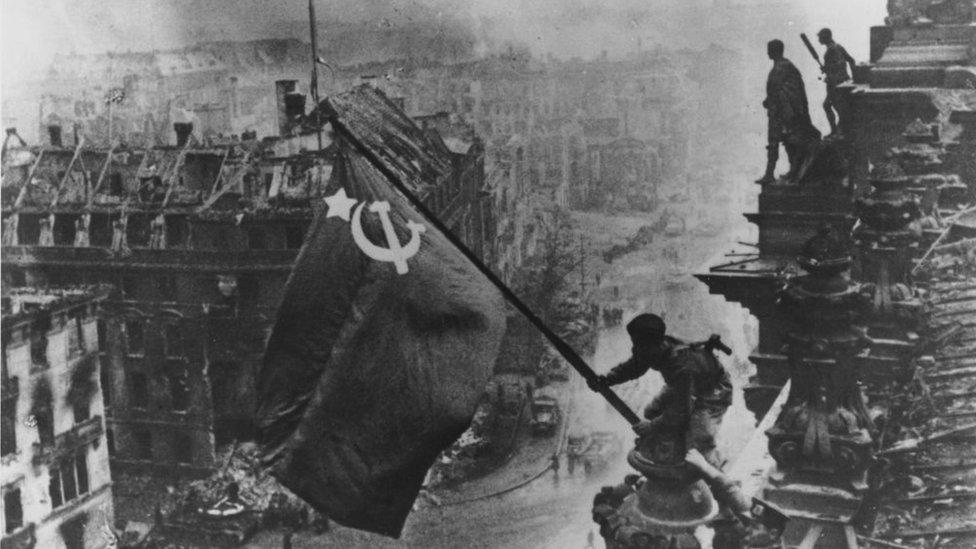 جنود روس يرفعون العلم الأحمر فوق أنقاض مبنى الرايخستاغ في برلين.
