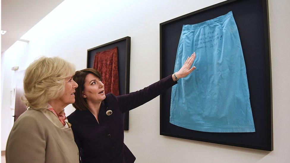رئيسة كوسوفو السابقة، عاطفة يحيى آغا، تأخذ دوقة كورنوال، كاميلا، في جولة على معرض يظهر تنانير ناجيات من الاغتصاب أثناء الحرب. الصورة التقطت في مارس 2016