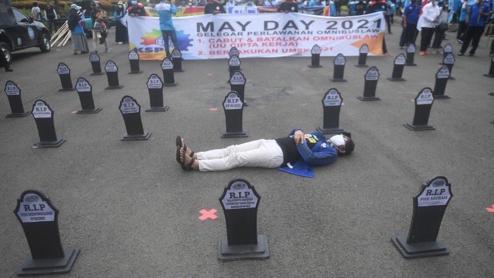 عضو بإحدى المنظمات العمالية الإندونيسية يستلقي خلال مسيرة عيد العمال