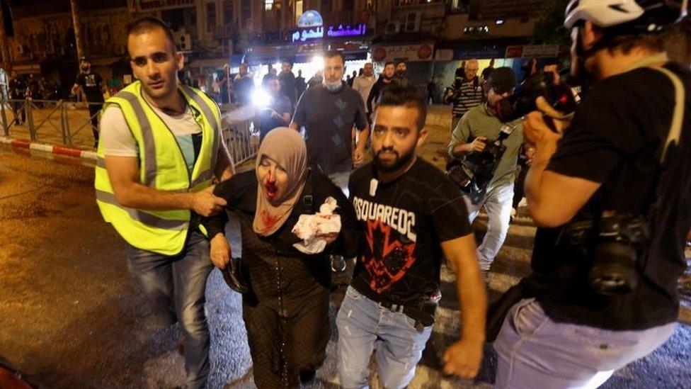 فلسطينيون ينقلون امرأة مصابة إلى مكان آمن