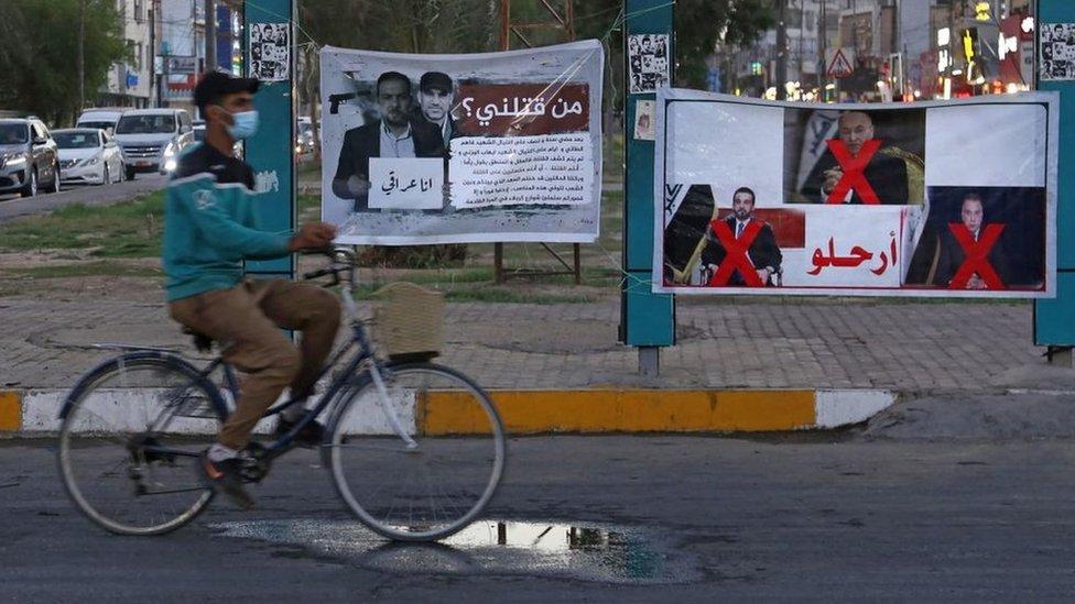 """لافتة في كربلاء تحمل صورة الناشط المقتول إيهاب الوزني كتب عليها: """"من قتلني؟"""""""