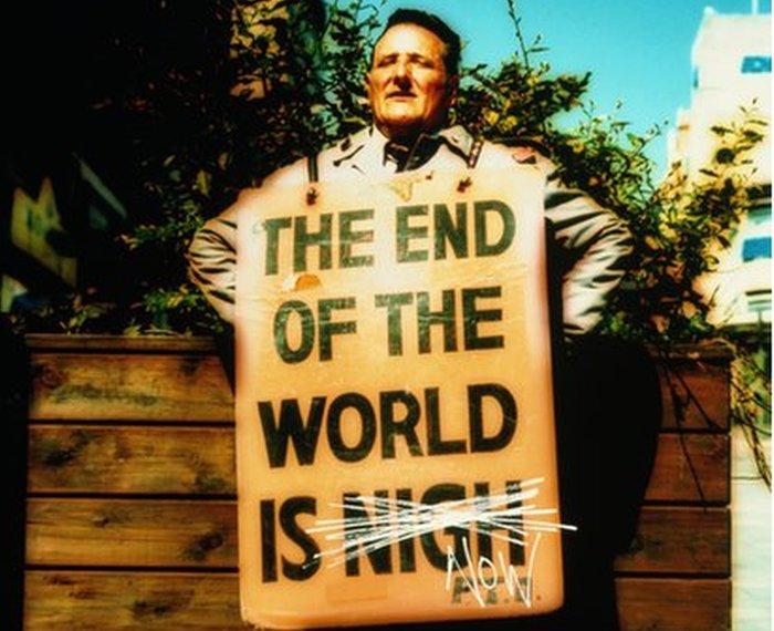 رجل يحمل يافطة عن اقتراب نهاية العالم